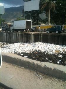 Envases de plumavit acumulados en un desagüe cerca del mar en Haití